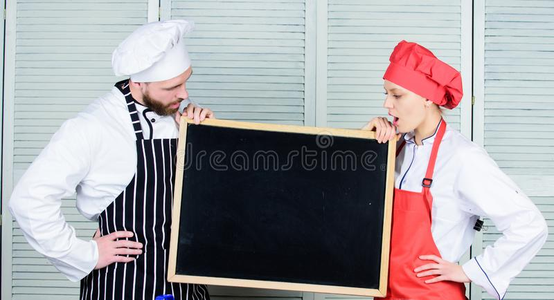 This class will inspire you. Master cook and prep cook giving cooking class. Chef and cook helper teaching master class. Couple of men and women holding empty royalty free stock photos