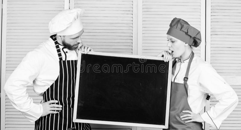 This class will inspire you. Master cook and prep cook giving cooking class. Chef and cook helper teaching master class. Couple of men and women holding empty stock images