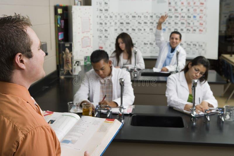 Classe da ciência de Raising Hand In do estudante fotografia de stock