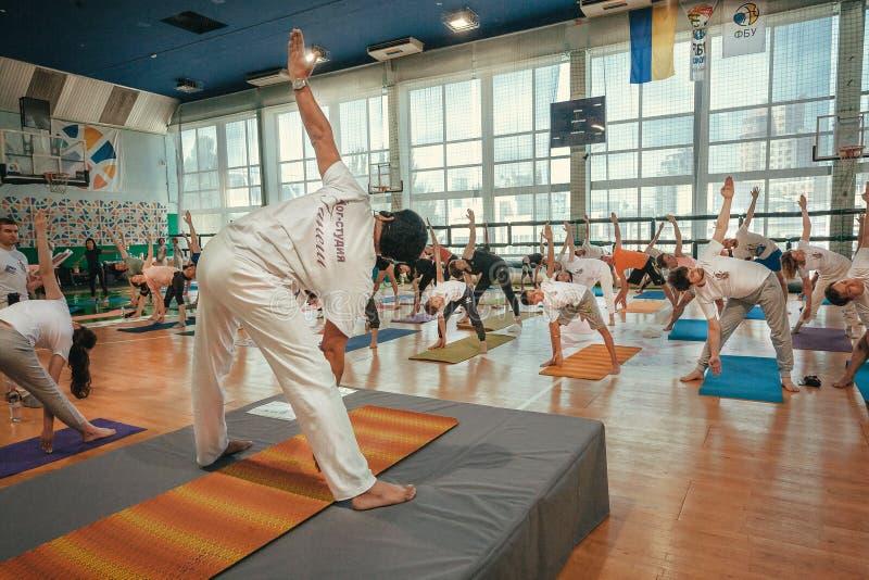 Classe da ioga com o professor que faz o exercício, curvaturas, práticas com asanas junto, treinando no dia do grupo imagem de stock