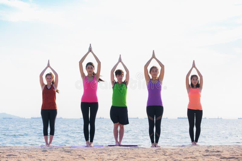 Classe da ioga na praia do mar na noite, grupo de pessoas que faz o namast imagem de stock royalty free