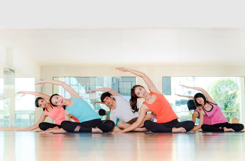 Classe da ioga na sala do estúdio, grupo de pessoas que faz o stre lateral assentado imagem de stock royalty free