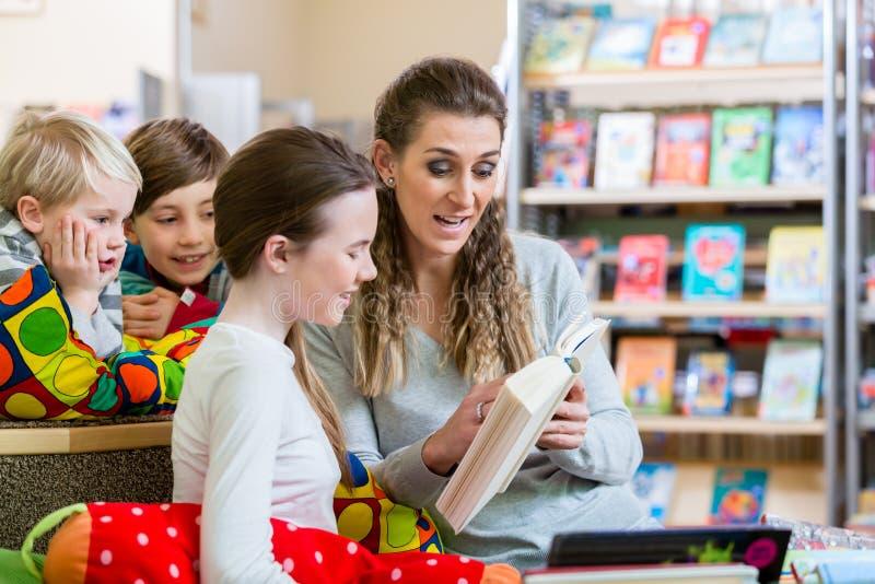 Classe de estudantes com seu professor na biblioteca escolar fotografia de stock