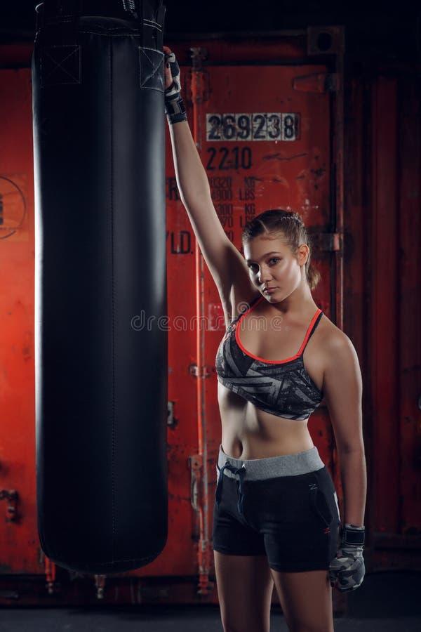 Classe de forme physique Gants de port de jeune belle femme de sports posant sur le fond du gymnase de boxe photographie stock