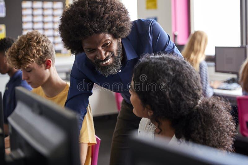 Classe de Working In Computer do estudante da High School de Helping Teenage Female do professor masculino foto de stock