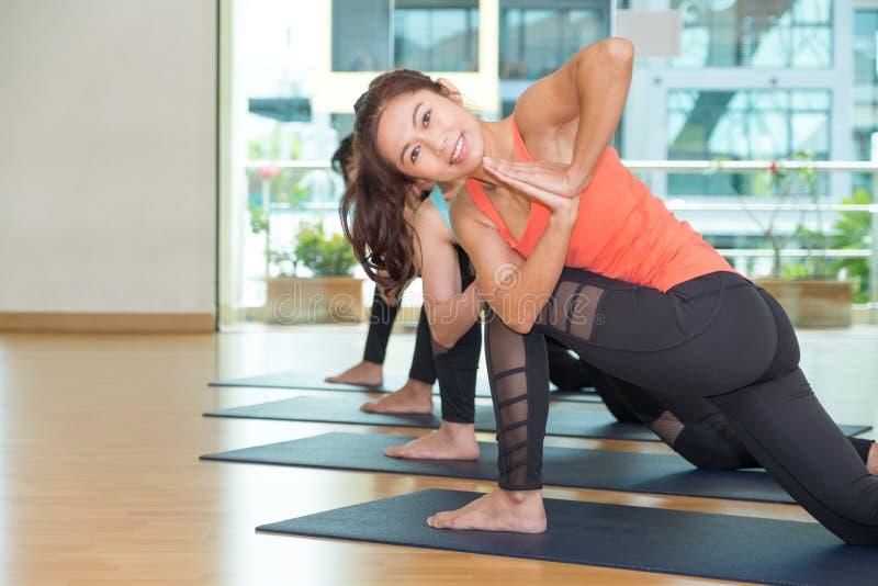 Classe de yoga dans la chambre de studio, groupe de personnes faisant Crescen tourné photographie stock libre de droits