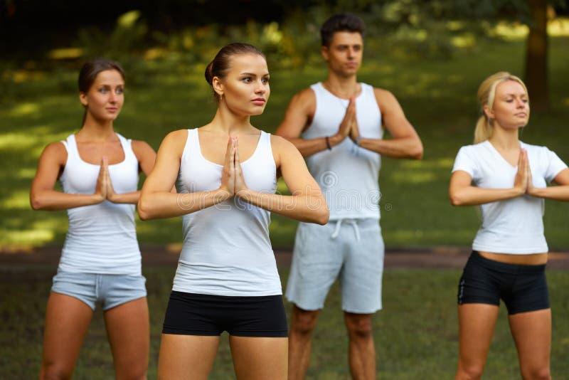Classe de yoga Groupe de personnes méditant au parc d'été photos libres de droits