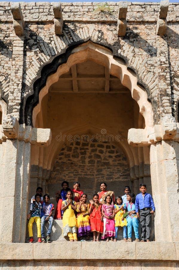 Classe di Chool con l'insegnante che posa sotto l'arco delle stalle dell'elefante a Hampi fotografie stock libere da diritti