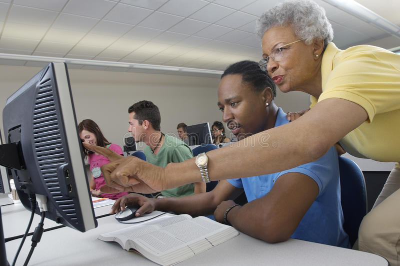 Classe do computador de Assisting Student In do professor fotos de stock royalty free