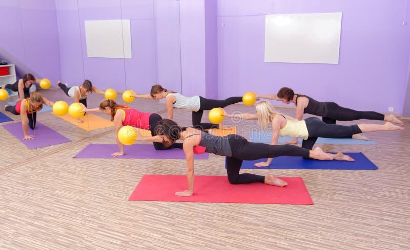 Classe dos pilates da ginástica aeróbica com bolas da ioga imagem de stock