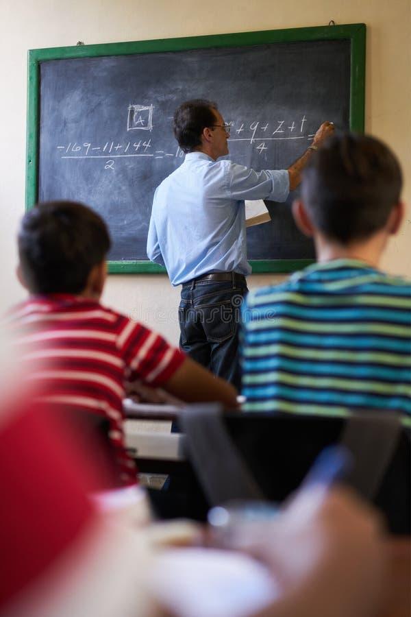 Classe envelhecida meio de At Blackboard Giving do professor de matemática imagens de stock royalty free