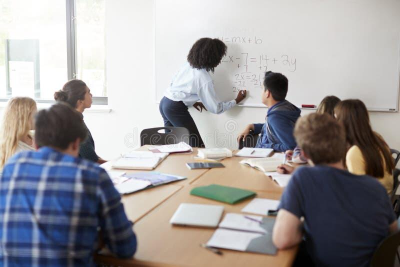 Classe fêmea das matemáticas de At Whiteboard Teaching do tutor da High School fotos de stock