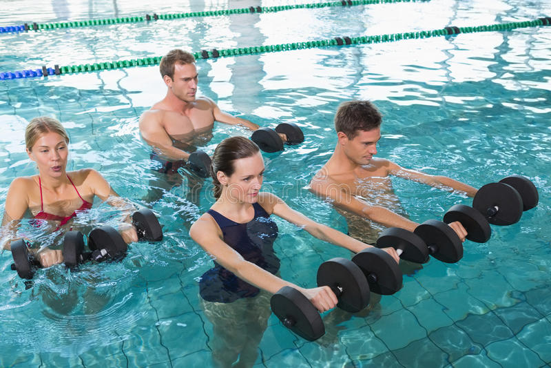 Classe heureuse de forme physique faisant l'aérobic d'aqua avec des haltères de mousse photo stock