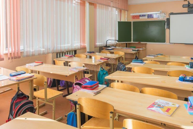 A classe interior na escola primária, as mesas dos estudantes e os professores da mesa embarcam no fundo fotos de stock