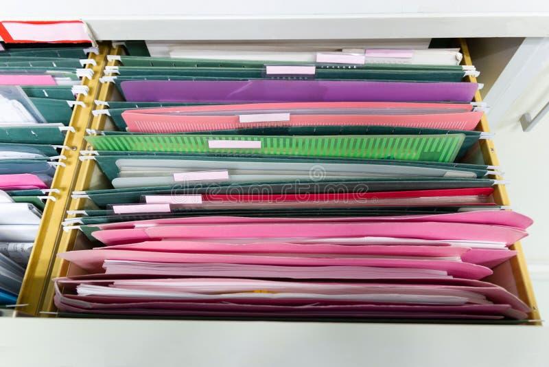 Classe le document des dossiers accrochants dans un tiroir dans une pile entière de pleins papiers, au bureau de travail images stock