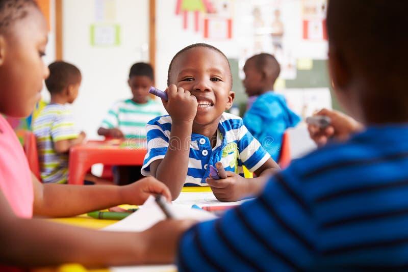 Classe préscolaire en Afrique du Sud, garçon regardant à l'appareil-photo images libres de droits
