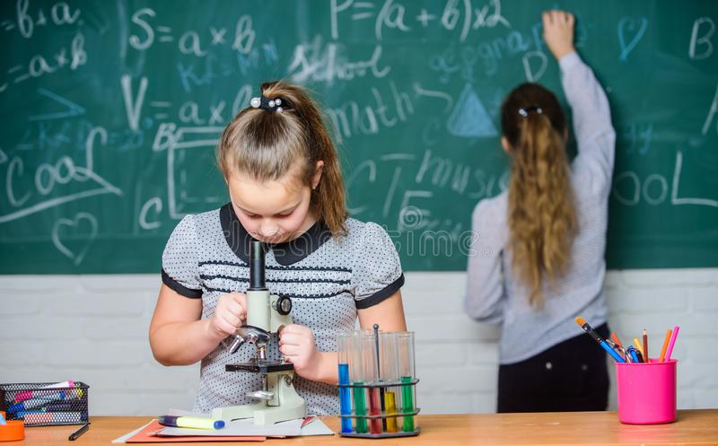 Classi di chimica Esperimento educativo I compagni di classe delle ragazze studiano la chimica Reazioni chimiche delle provette d fotografie stock
