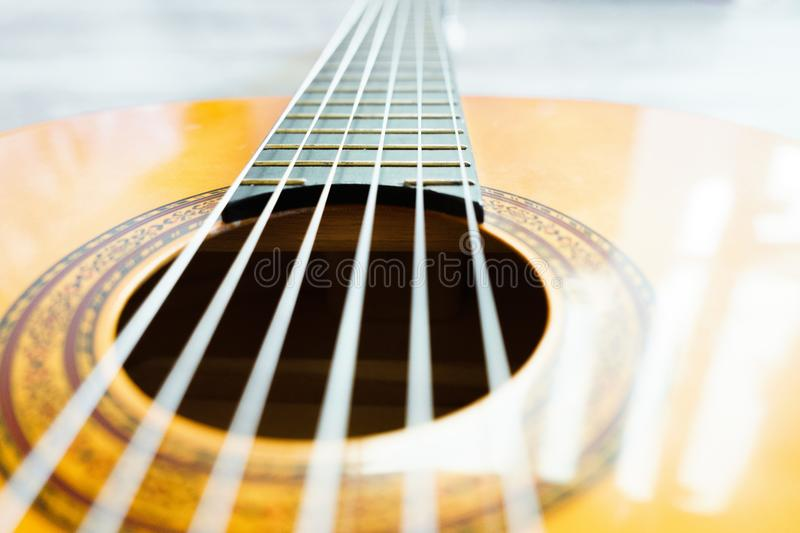 Classic acoustic guitar at weird and unusual perspective closeup. Six strings, free frets, sound hole and soundboard. stock photo
