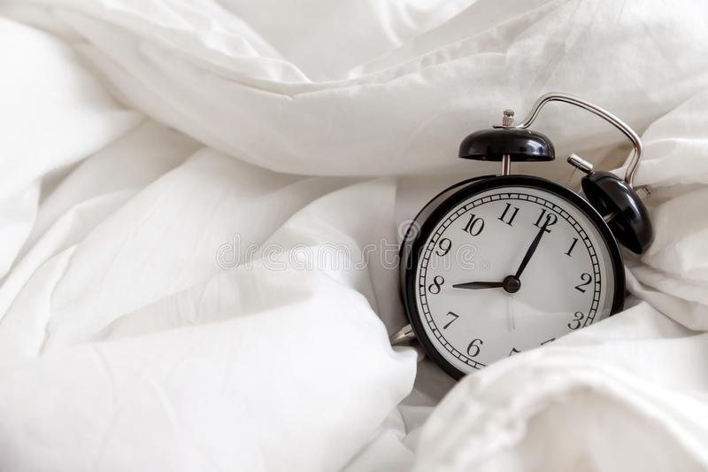 Classic alarm clock in bed, concept of morning routine. Wake up on time stock photo