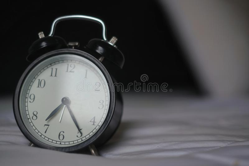 Classic alarm clock on the bed stock photo
