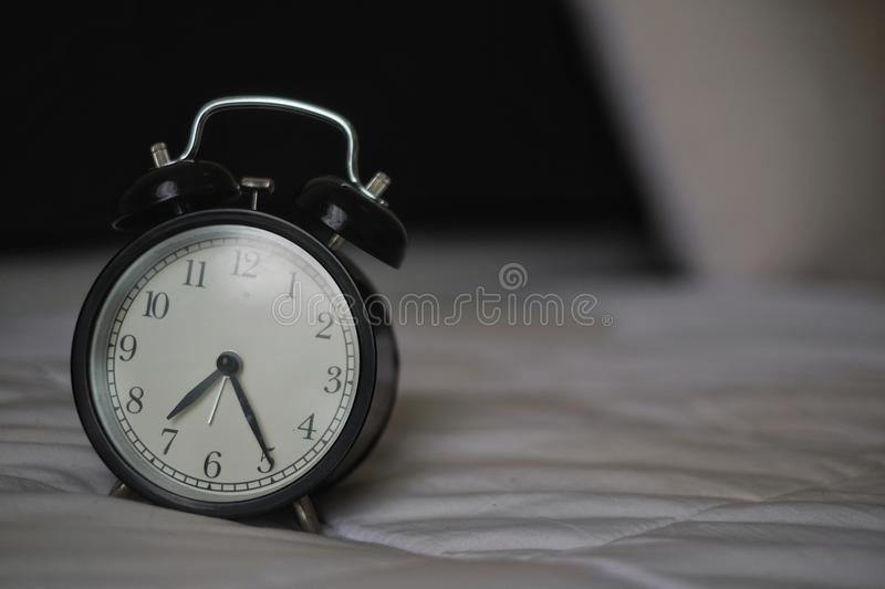 Classic alarm clock on the bed royalty free stock images