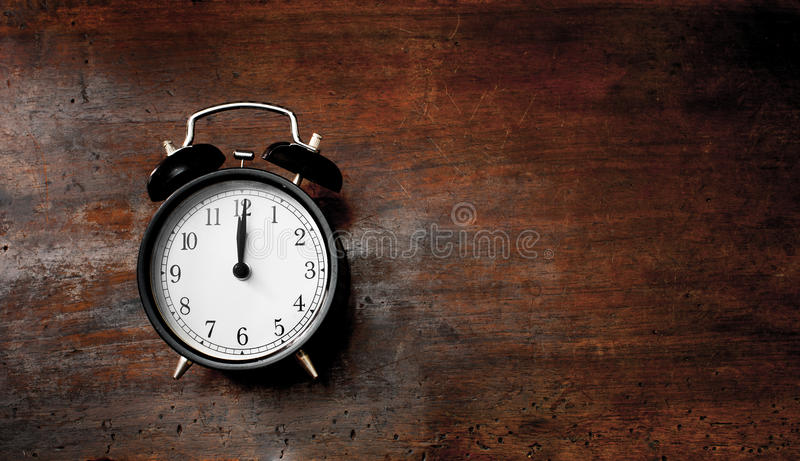 Classic alarm clock noon time on wood. Classic old black alarm clock noon time on wooden scraped table royalty free stock image