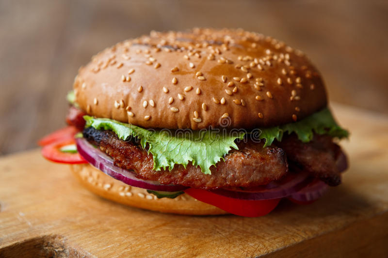 Classic american burger, fast food on wood background royalty free stock images