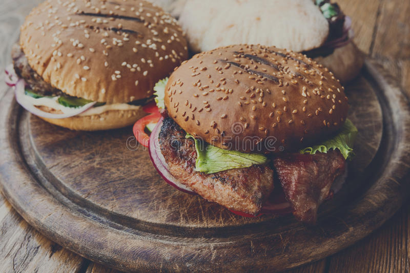 Classic american burgers, fast food on wood background royalty free stock photos