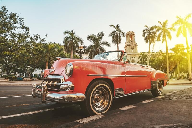 Classic American car against the background of palm trees in bright sun in the evening in Havana against the background of. Classic American car against the royalty free stock images
