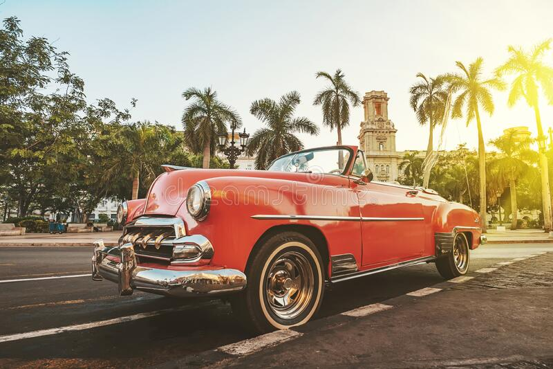 Classic American car against the background of palm trees in bright sun in the evening in Havana against the background of. Havana, Cuba. Classic American car royalty free stock images