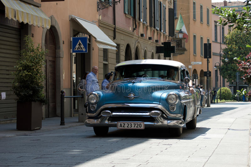 Classic American car at Mille Miglia 2016. A blue American sedan from the fifties passing through Tasso street (Bergamo, Italy) before the crowd during the 2016 royalty free stock photos