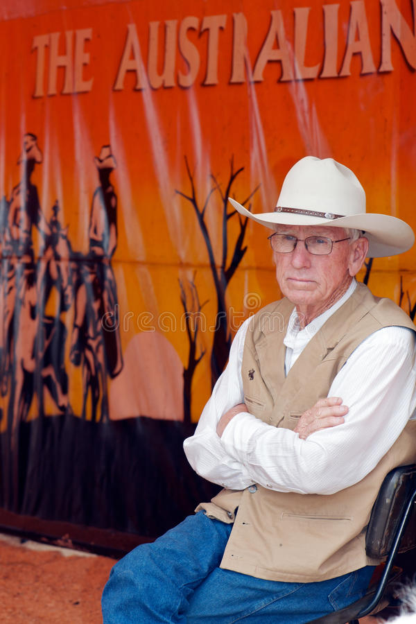 Classic Australian Man. Classic senior Australian man with stockman's hat sitting in front of outback poster at the Outback Pony Ride booth, Ekka, August 2011 stock photos