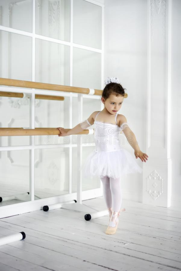Classic ballet dancer child posing at barre on rehearsal room background. 6 years old girl in white ballet clothes with mirrors on royalty free stock image