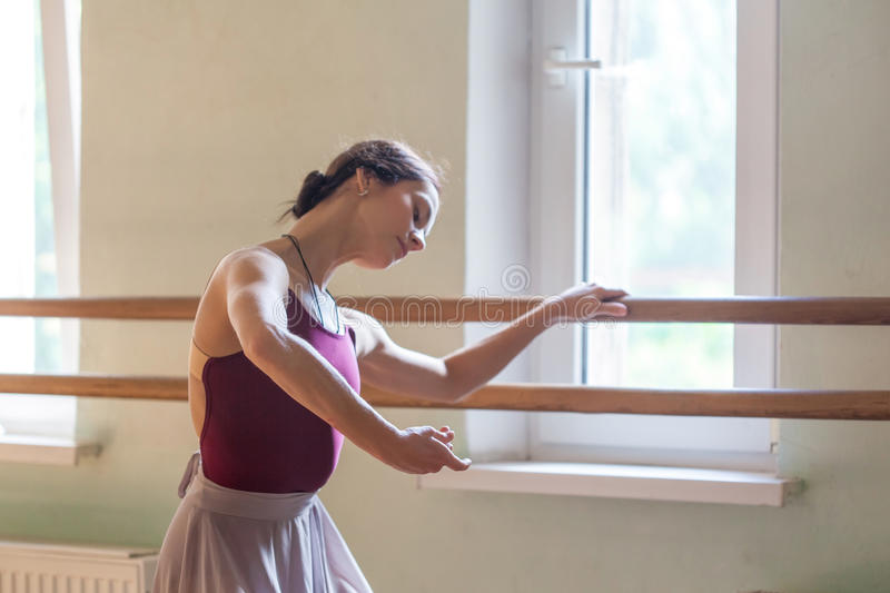 Classic ballet dancer posing at barre on rehearsal. The classic ballet dancer posing at ballet barre on a rehearsal room background royalty free stock images