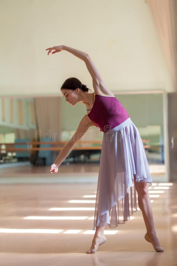 Classic ballet dancer posing at barre on rehearsal. The classic ballet dancer posing at ballet barre on a rehearsal room background stock images