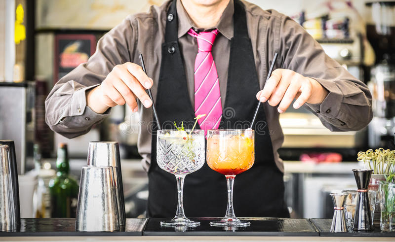 Classic bartender serving gin tonic and tequila sunrise cocktails at bar royalty free stock images