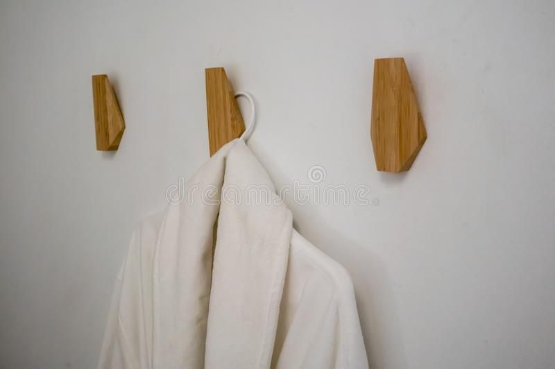 Classic bathrobe hanging on wooden abstract wall hook mounted ag stock photography