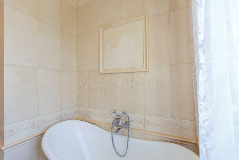 Classic Bathroom In Beige Tones Curved Bath Tub Large Beige Tile
