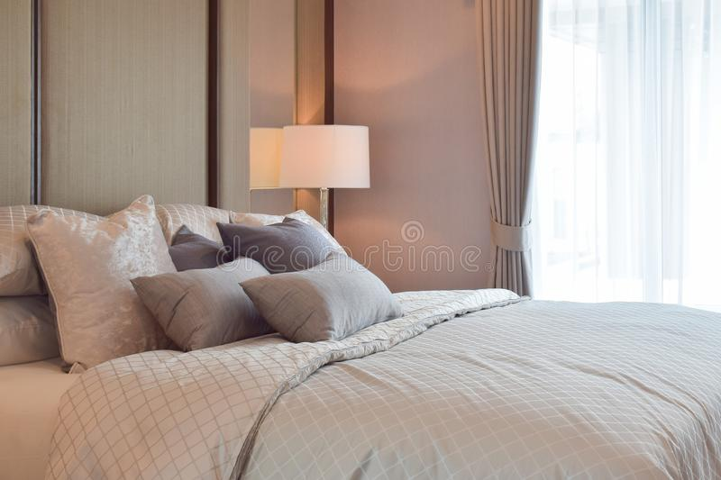 Classic bedroom interior with pillows and reading lamp on bedside table.  stock photos