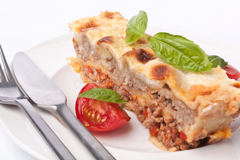 Classic Beef Lasagna. Slice with Tomatoes and Basil Close up stock photo