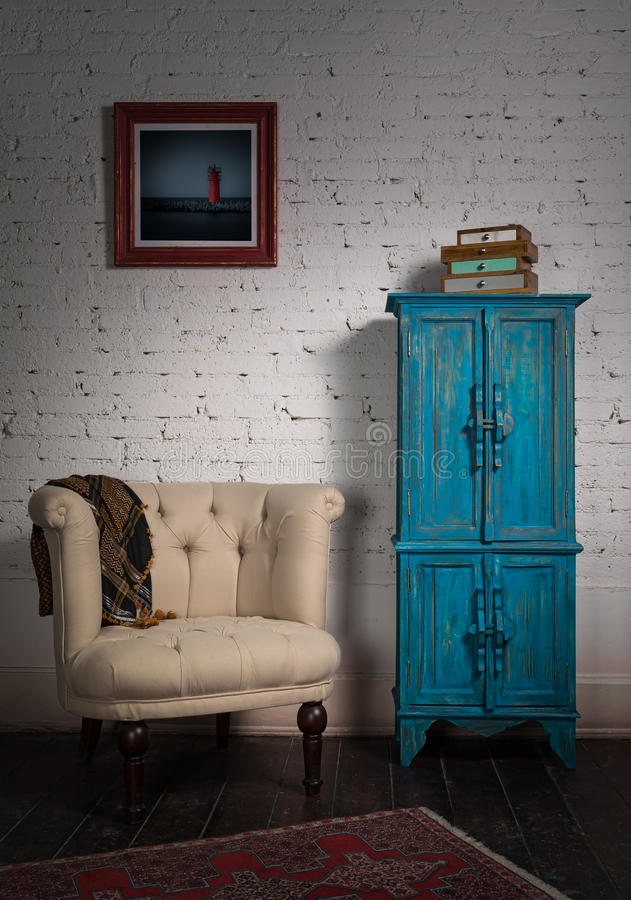 Classic beige armchair, blue vintage cupboard, scarf and painting royalty free stock images