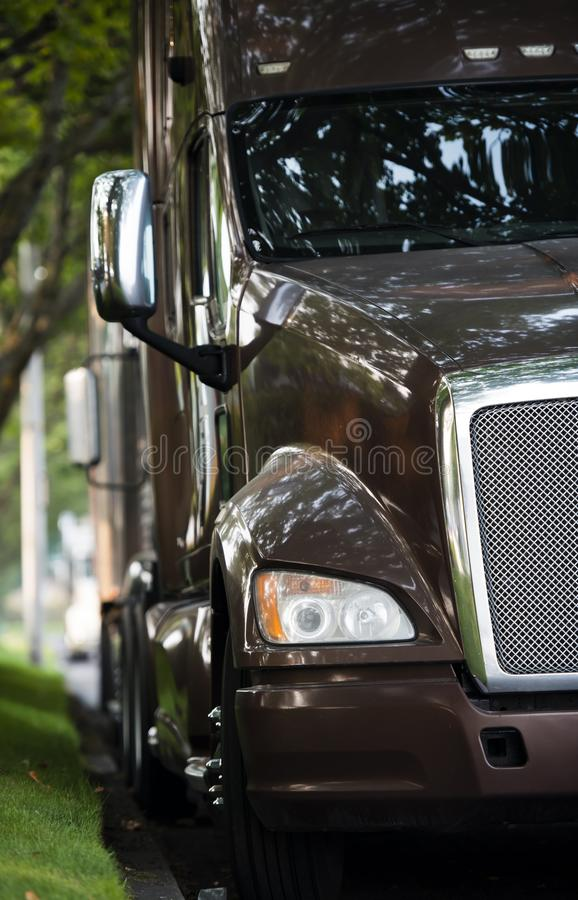 Classic big rig bonnet dark brown semi truck tractor standing in front of another semi trucks on the road side with green trees. Classic shiny big rig bonnet royalty free stock photos