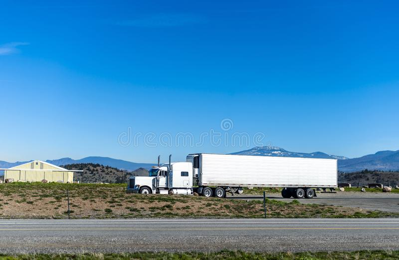 Classic big rig semi truck transporting cargo in refrigerated semi trailer driving on the road in Utah. Classic big rig bonnet American idol white long haul semi royalty free stock photo