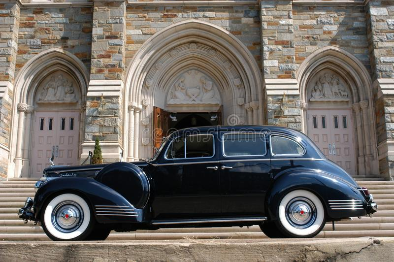 Classic Black Car Parked In Front Of Grey Concrete Building royalty free stock photos