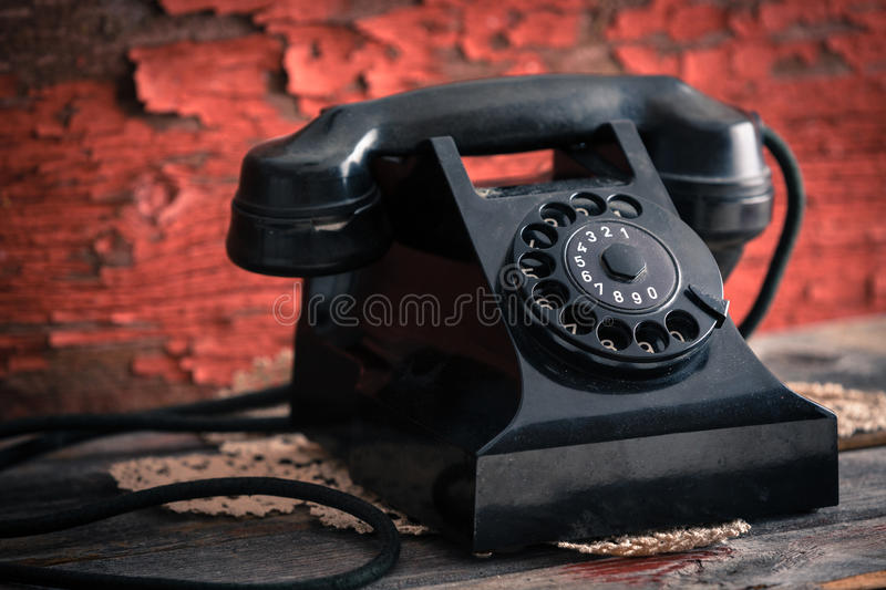 Classic black dial-up rotary telephone. Close up side view of an old classic black dial-up rotary telephone against a grunge wooden wall with peeling red paint royalty free stock photography