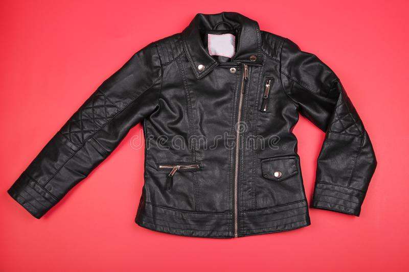 Classic black leather bikers` kids female jacket on red bakground royalty free stock photos