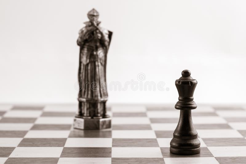 Classic black queen and the same piece in the form of medieval f. Igure on the background. Selective focus on classic piece royalty free stock images