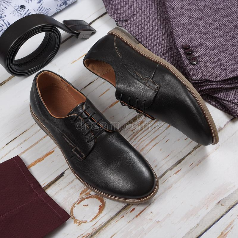 Classic black shoes, belt and clothes on wooden background. Vintage royalty free stock images