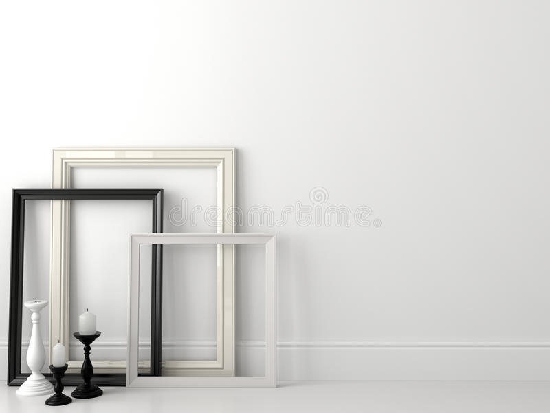Classic black and white frames on white wall. Classical composition in black and white colors, consisting of frames and candlesticks royalty free stock image