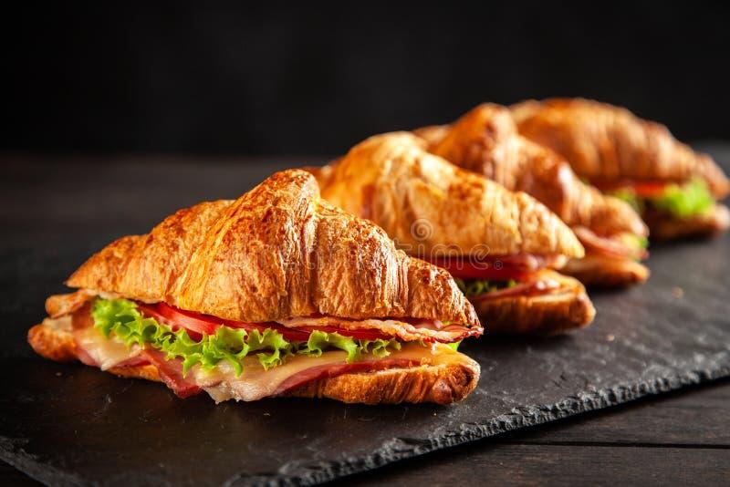 Classic BLT croissant sandwiches. On dark background stock image